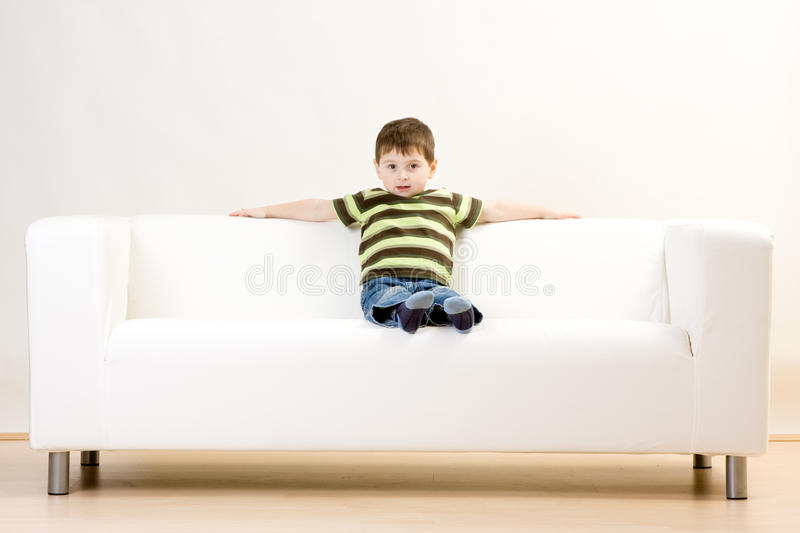 Boy sitting on couch royalty free stock image
