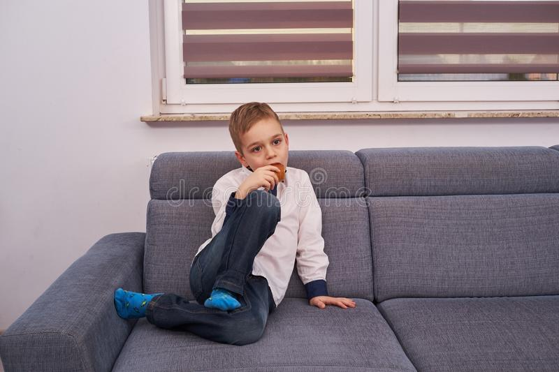 The boy is sitting on the couch and eating bread stock images