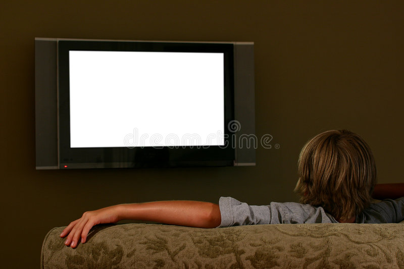 Boy sitting on couch watching widescreen television stock images