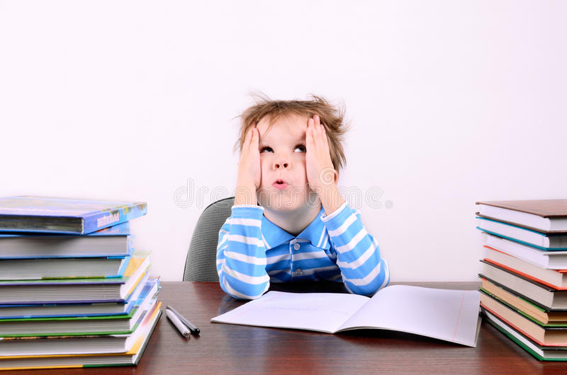 Boy sitting at a desk and looking up. Little boy with disheveled hair sitting at a desk and looking up. boy 5 years. on the desk a lot of books. photo taken on a stock photo