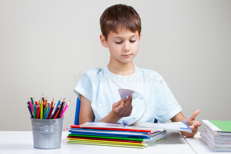 Boy sitting at desk with pile of school books and notebooks and doing homework at home royalty free stock photography