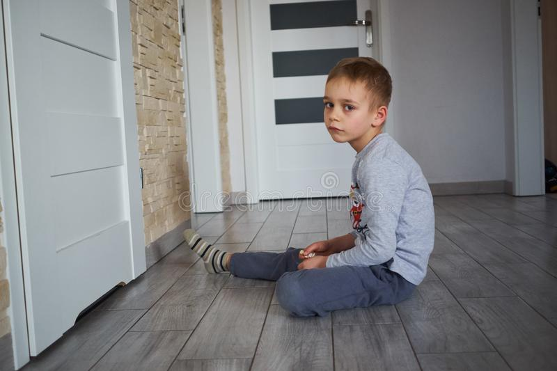 The boy is sitting on the floor stock photo