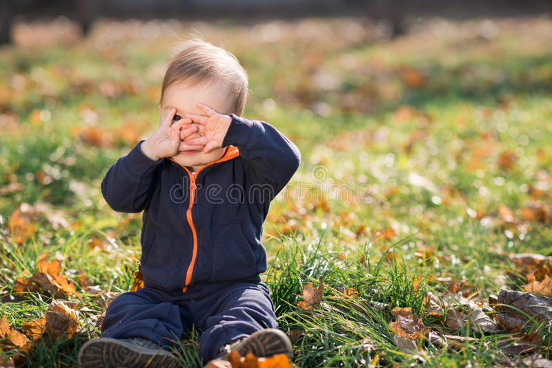 Download Boy Sitting On The Grass And Hides Stock Photo - Image: 34887878
