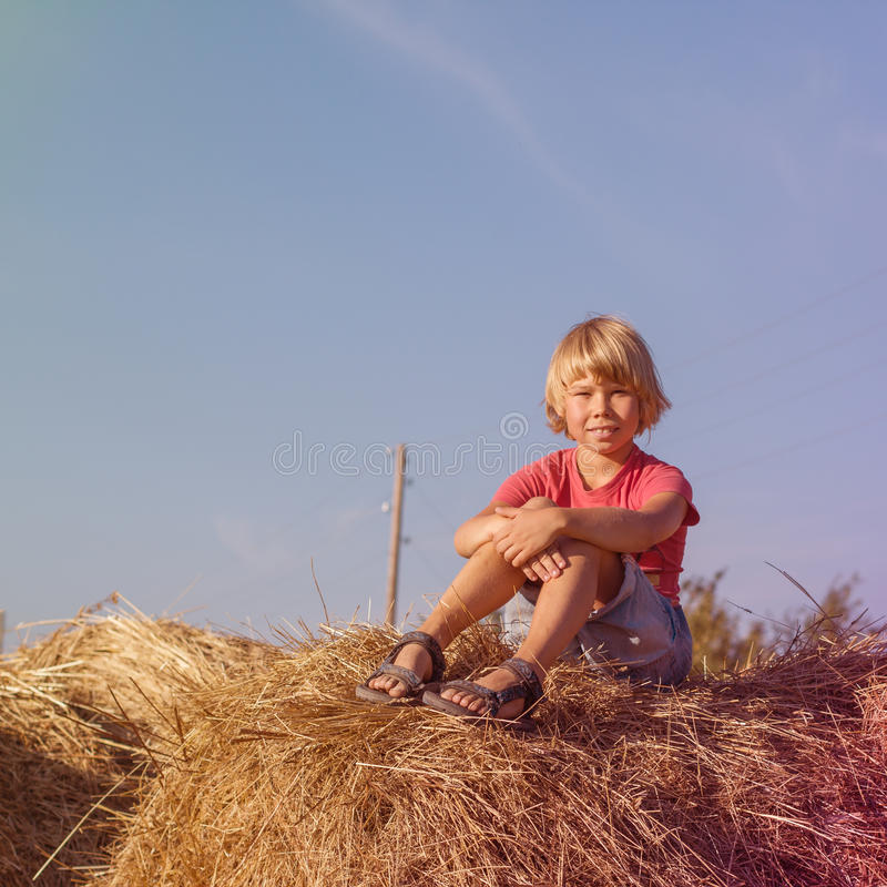 Boy sitting on a haystack stock image