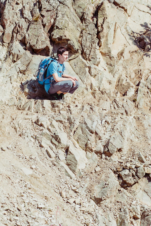 Boy sitting on the hillside. Teenager sitting on the rocky hillside stock image
