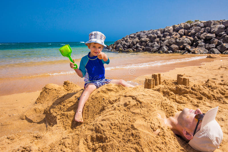 Boy sitting on his father covered by sand on the Jandia beach, Fuerteventura, Canary Islands, Spain stock images