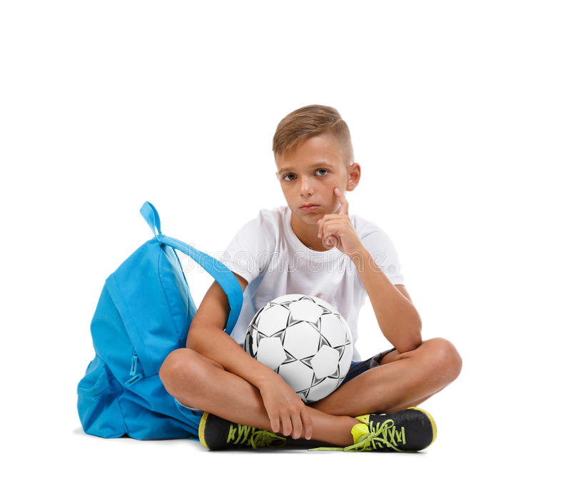 A boy sitting in the lotus position. A sportive kid with bright satchel and soccer ball isolated on a white background. A boy with a ball. A little schooler stock photography