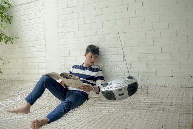 Boy Sitting Near Radio Holding White Catalog royalty free stock images