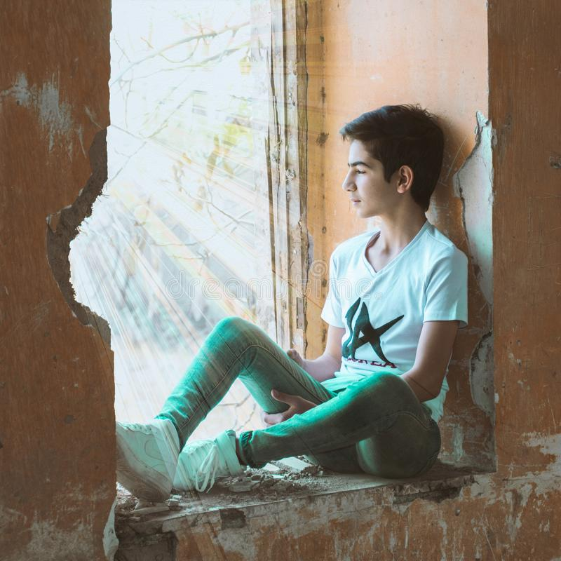 Boy Sitting Near Wall stock images