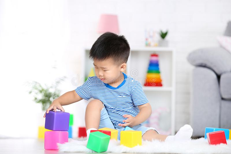 Boy sitting and playing with plastic toys. Beautiful boy sitting and playing with plastic toys at home royalty free stock photo