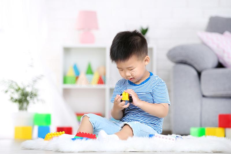 Boy sitting and playing with plastic toys. Beautiful boy sitting and playing with plastic toys at home royalty free stock photography