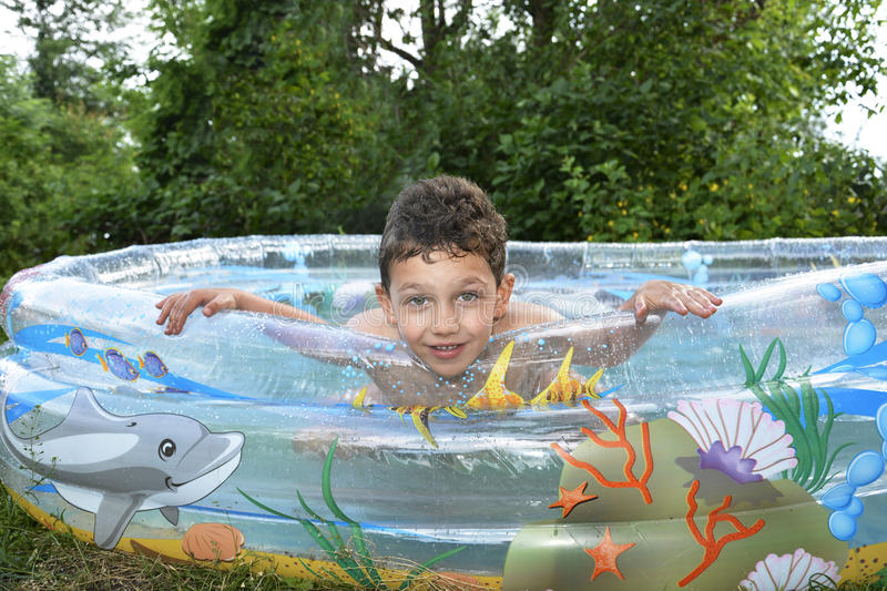 Boy sitting in the pool. stock images