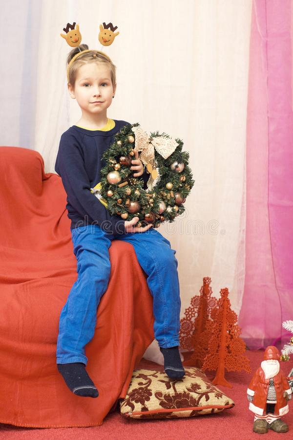Boy sitting on red chair with Christmas wreath in his hands royalty free stock photos