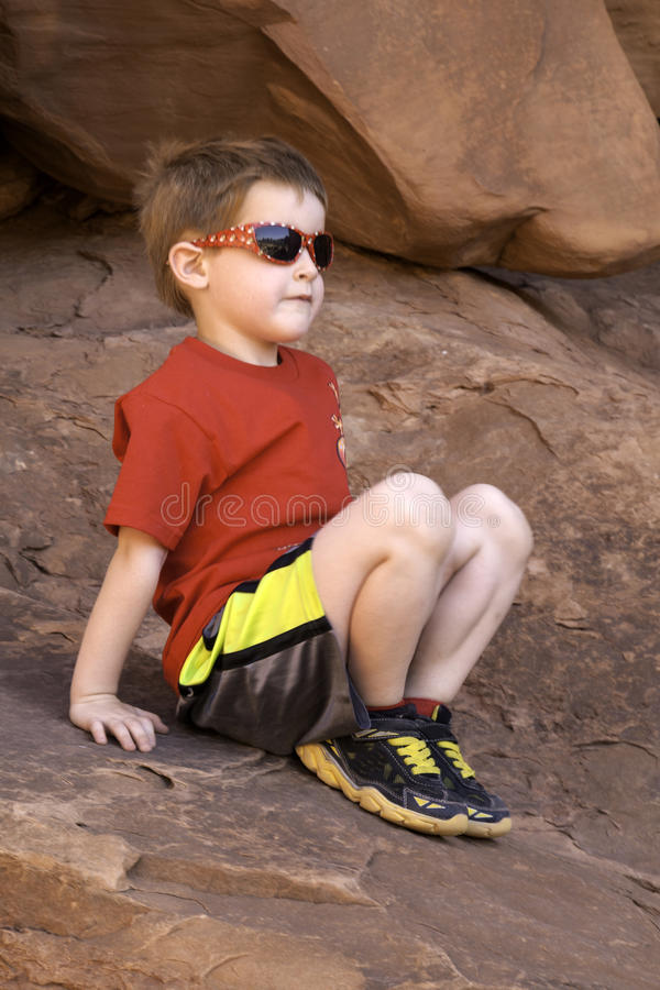 Boy sitting on Rock stock photos