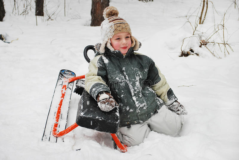 Boy sitting in the snow with sledges.