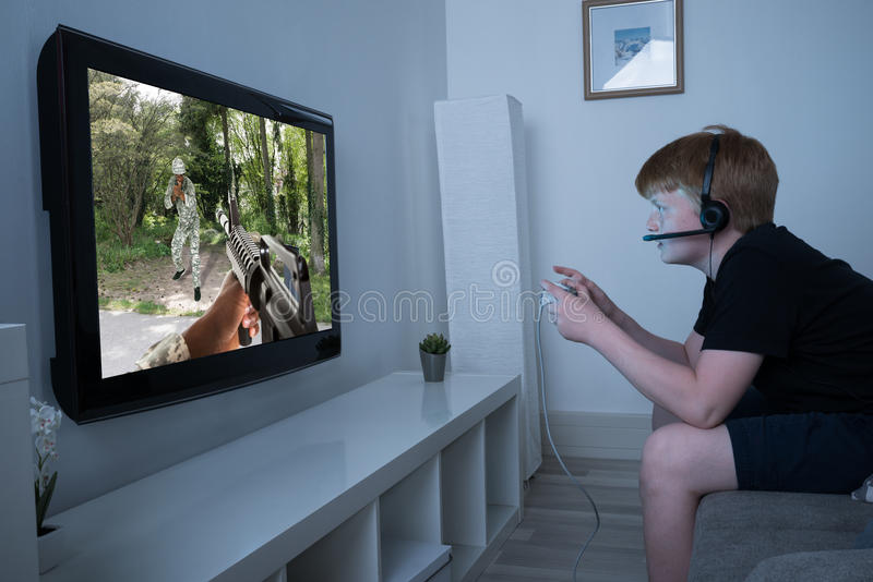 Boy Playing Action Game On Television stock photo
