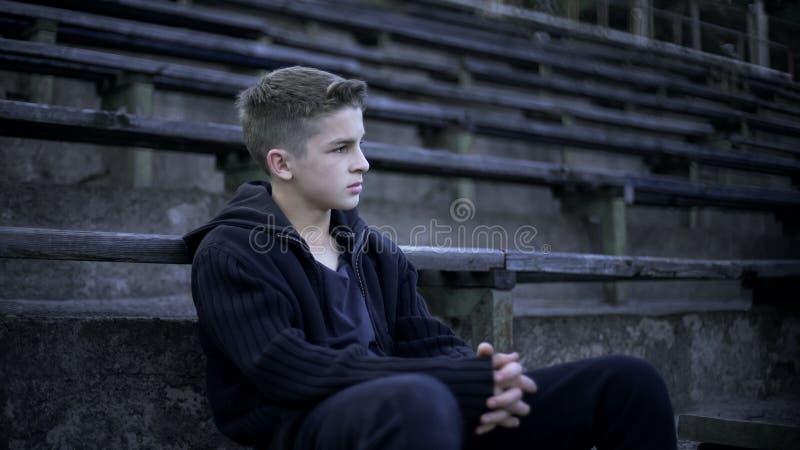 Boy sitting on stadium tribune, devastation and poverty around, city after war stock photo