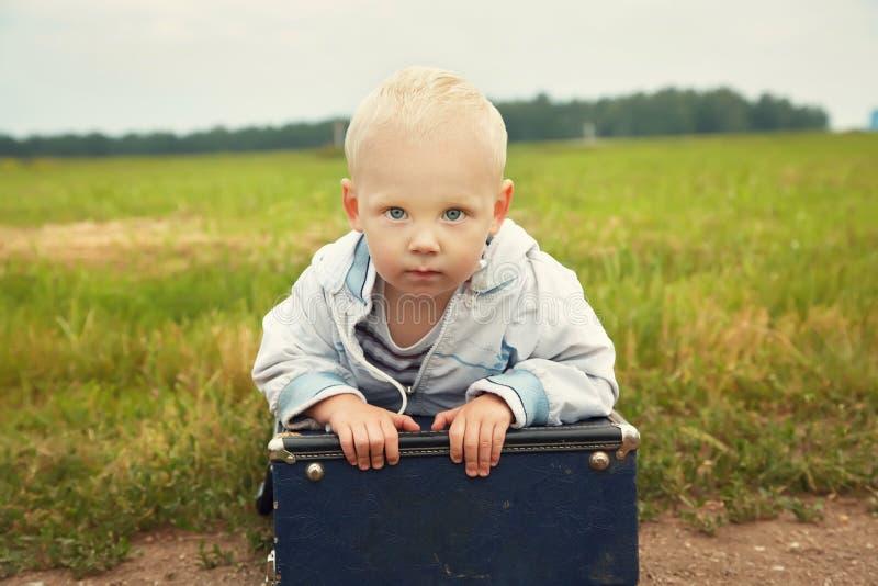 Boy sitting on a suitcase. child traveler. Little boy sitting on a suitcase. child traveler royalty free stock photography