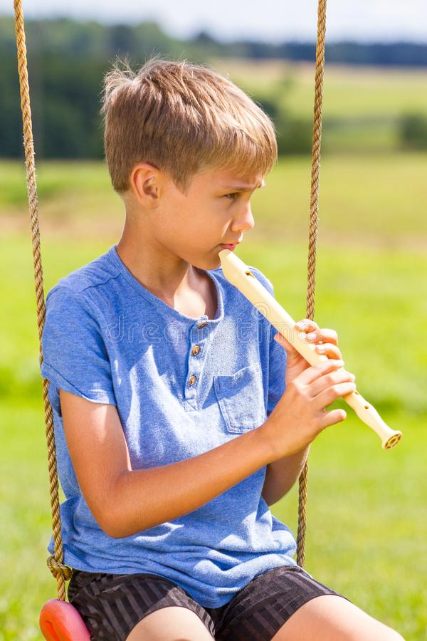 Boy sitting on swings and playing flute outdoors.  stock image