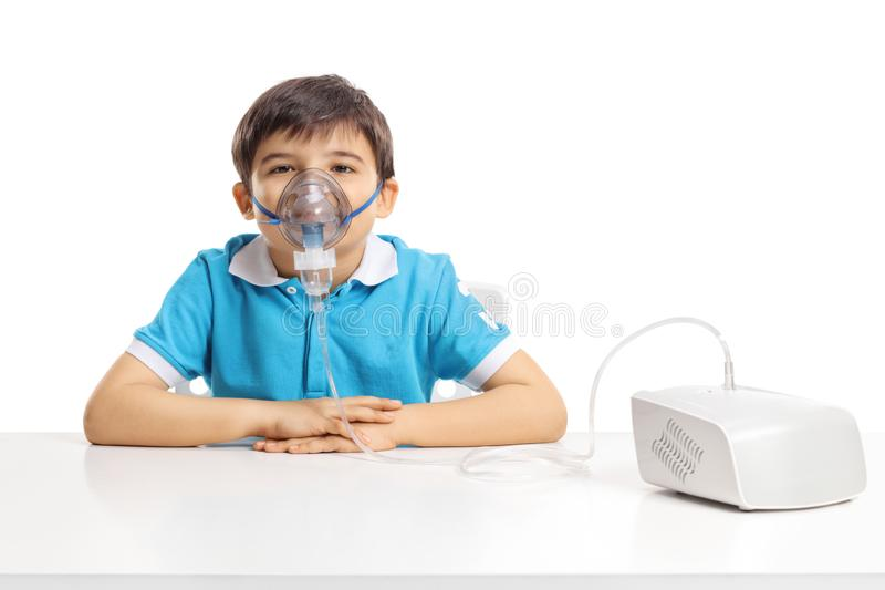 Boy sitting at a table with inhaling mask royalty free stock images