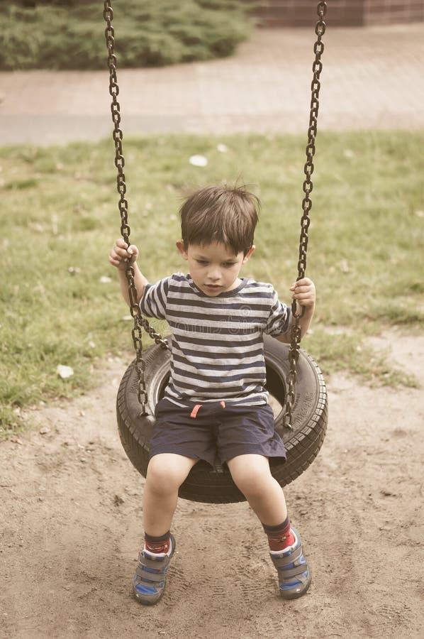 Boy sitting on tire swing set stock images