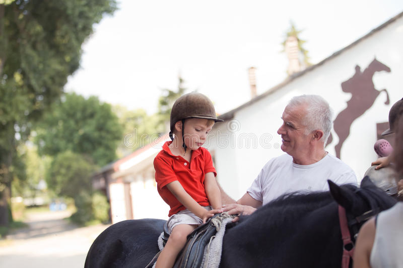 A boy sitting on top of a black horse listening to his grandfather's instruction royalty free stock photo