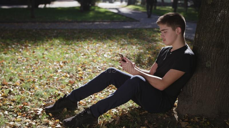 Boy is sitting under a tree with a smartphone royalty free stock image