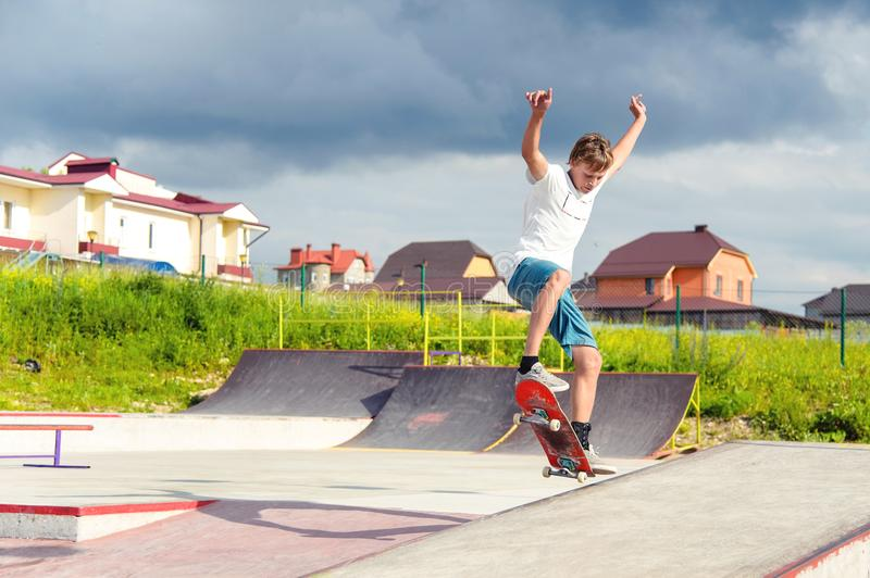 A boy in a skate park doing a trick on a skateboard. Boy skateboarder in a skate park doing an ollie trick on a skateboard against a sky and thunderclouds stock photos