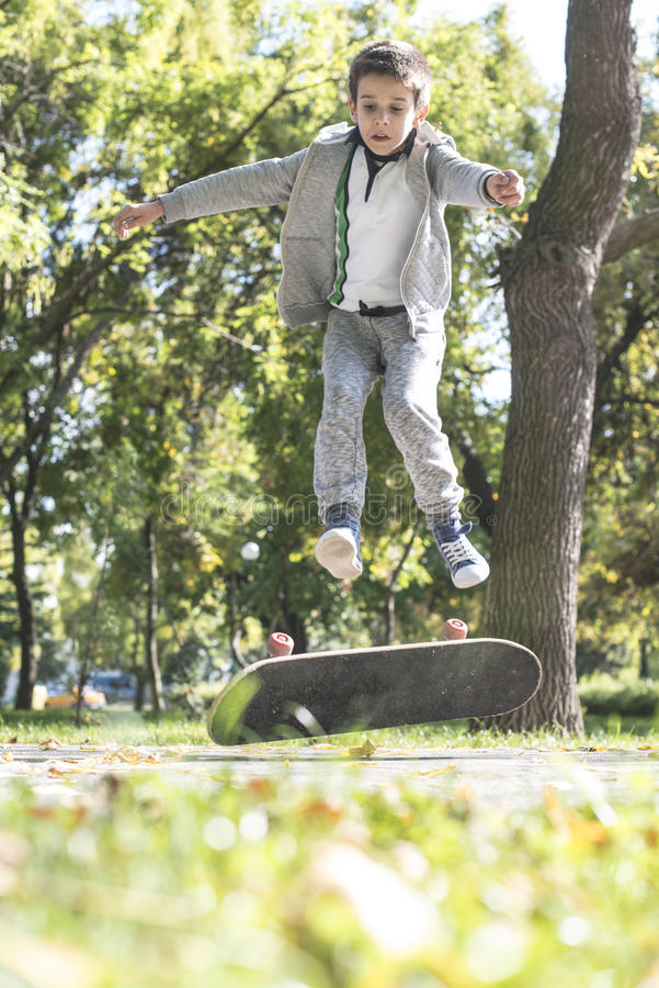 Boy with skateboard. In the park. Autumn leaves royalty free stock photography