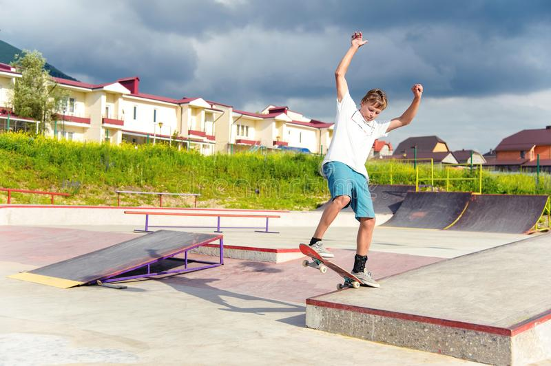 A boy in a skate park doing a trick on a skateboard. Boy skateboarder in a skate park doing an ollie trick on a skateboard against a sky and thunderclouds stock image