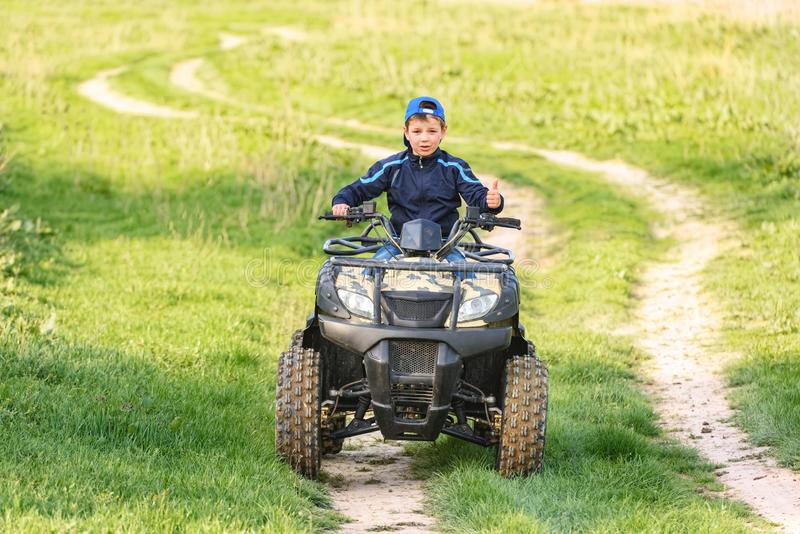 The boy skates on a quad bike in a beautiful area royalty free stock photography