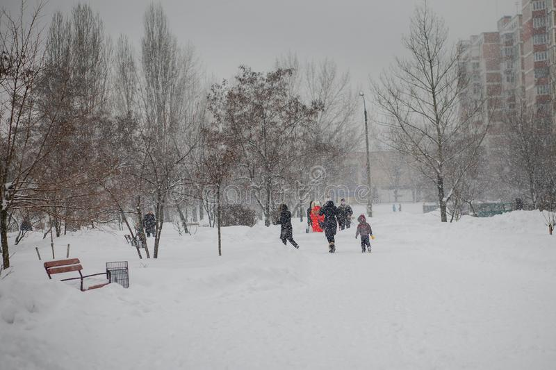 A boy in a ski suit on a snow mountain with a sled. The child is riding a sledge scooter . Active games on the street. Healthy stock photos