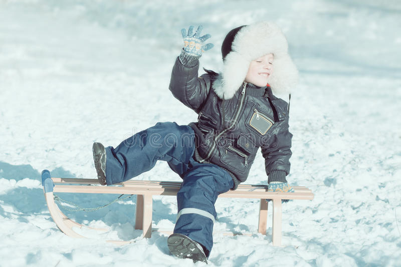Boy on sled with close eyes enjoying the winter stock photos