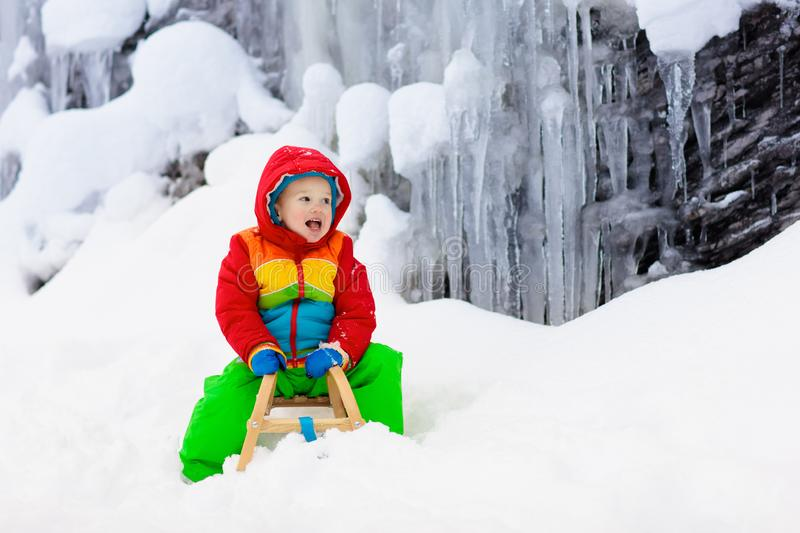 Boy on sled ride. Child sledding. Kid on sledge. Little boy enjoying a sleigh ride. Child sledding. Toddler kid riding a sledge. Children play outdoors in snow royalty free stock images