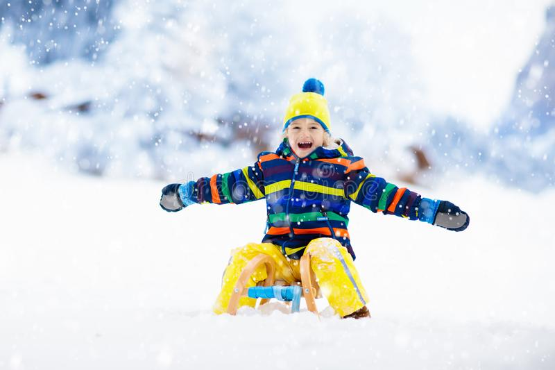 Boy on sled ride. Child sledding. Kid on sledge stock photo