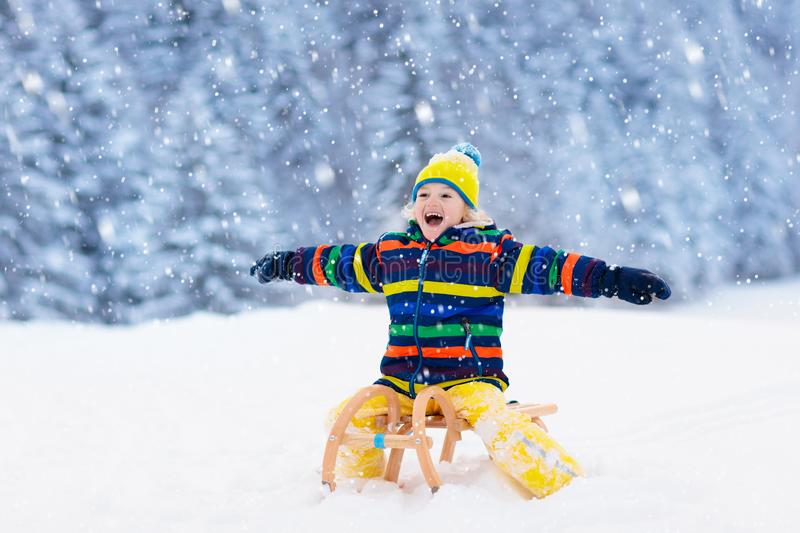 Boy on sled ride. Child sledding. Kid on sledge. Little boy enjoying a sleigh ride. Child sledding. Toddler kid riding a sledge. Children play outdoors in snow stock photography