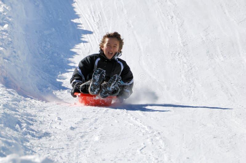 Boy Sledding Down the Hill stock photo