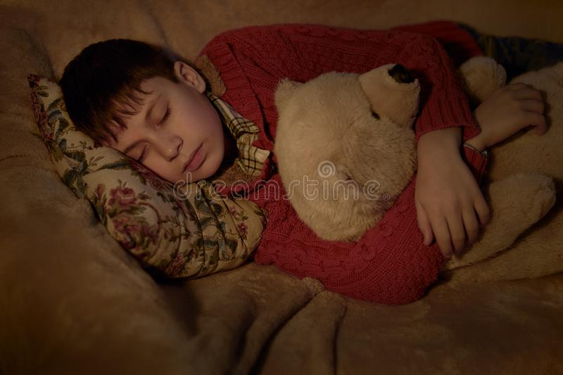 Boy sleep in bed with bear toy royalty free stock photo
