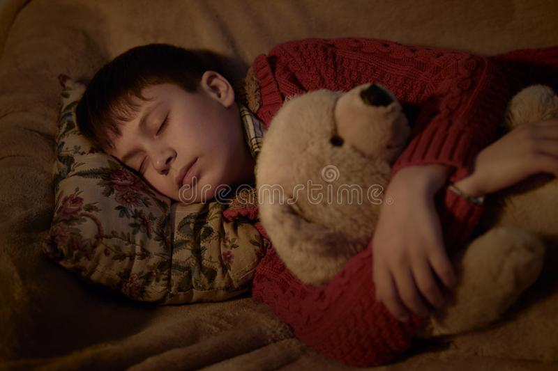 Boy sleep in bed with bear toy royalty free stock images