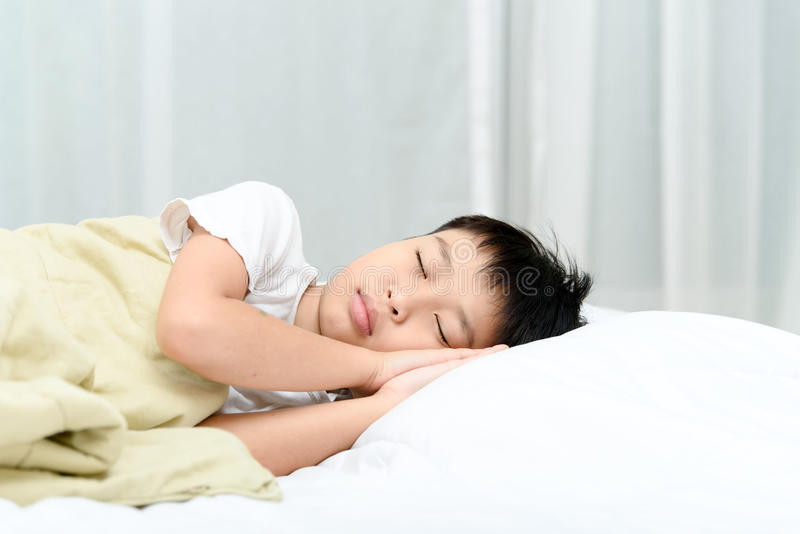 Boy sleep on bed. Young Thai boy sleep on the white bed in the bedroom stock photos