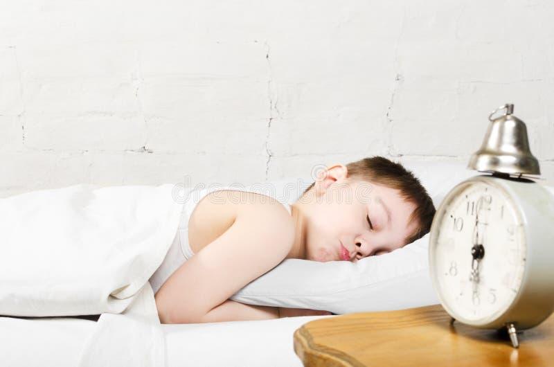 Boy sleeping in bed stock image