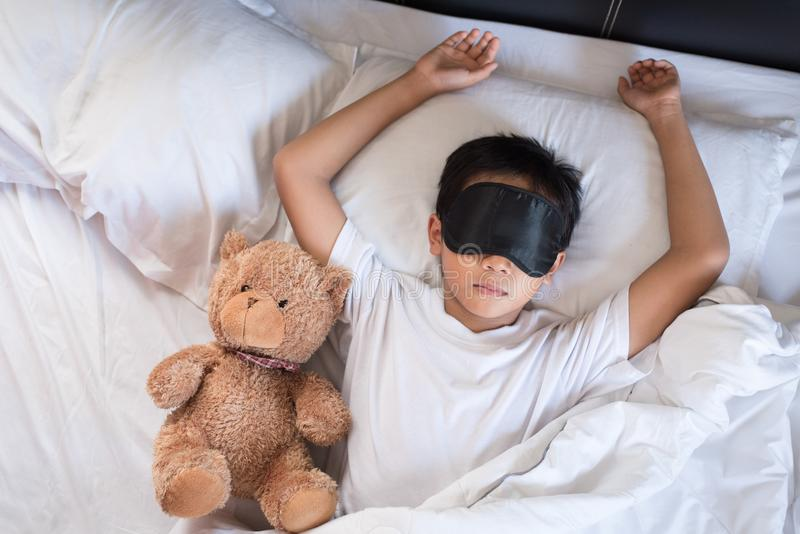 Boy sleeping on bed with teddy bear white pillow and sheets wearing sleep mask. Boy fall asleep in morning.sleep concept royalty free stock photos