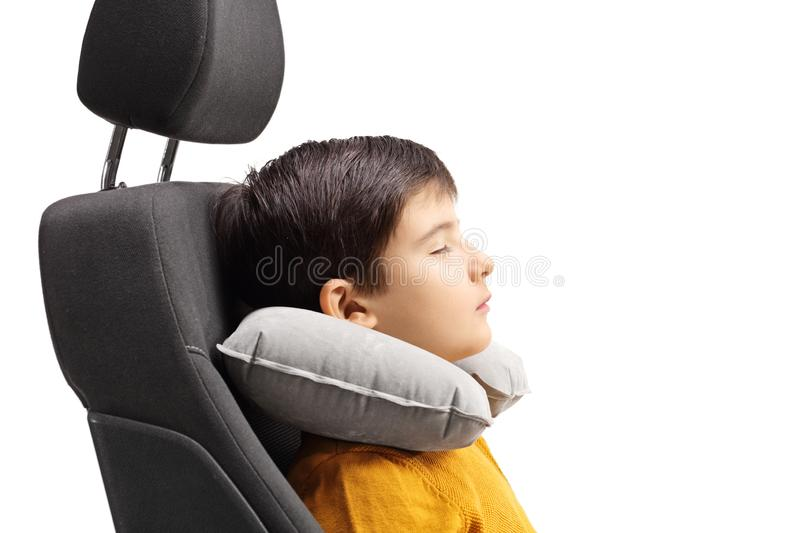Boy sleeping in a car seat with a travel pillow around his neck. Isolated on white background stock photos