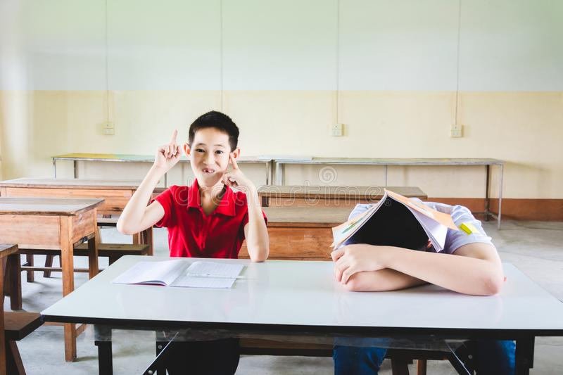 Boy is sleeping in class but another one hand up to answer the question stock image