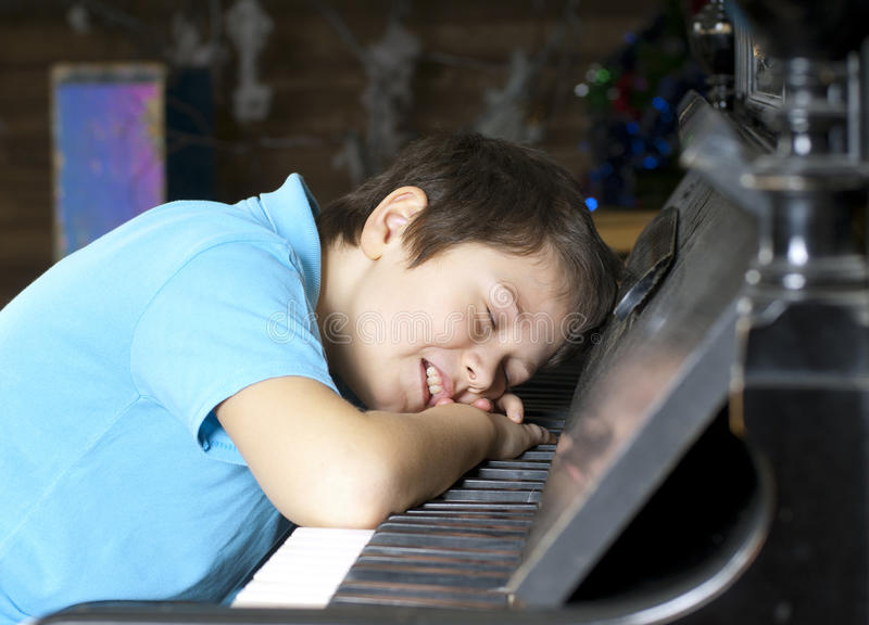 Boy is sleeping at the piano royalty free stock photo