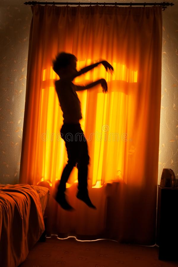 Boy sleepwalker jumping from bed royalty free stock photography