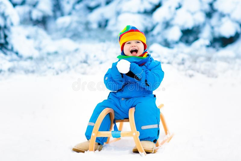 Boy on sleigh ride. Child sledding. Kid with sledge. Little boy enjoying a sleigh ride. Child sledding. Toddler kid riding a sledge. Children play outdoors in stock photography