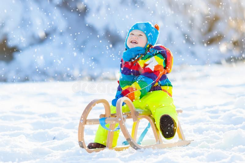 Boy on sleigh ride. Child sledding. Kid with sledge. Little boy enjoying a sleigh ride. Child sledding. Toddler kid riding a sledge. Children play outdoors in royalty free stock photo