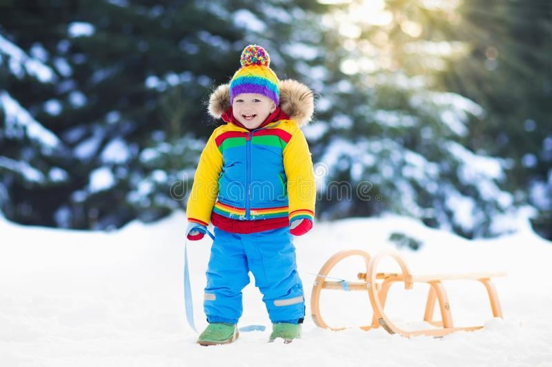 Boy on sleigh ride. Child sledding. Kid with sledge. Little boy enjoying a sleigh ride. Child sledding. Toddler kid riding a sledge. Children play outdoors in stock photo