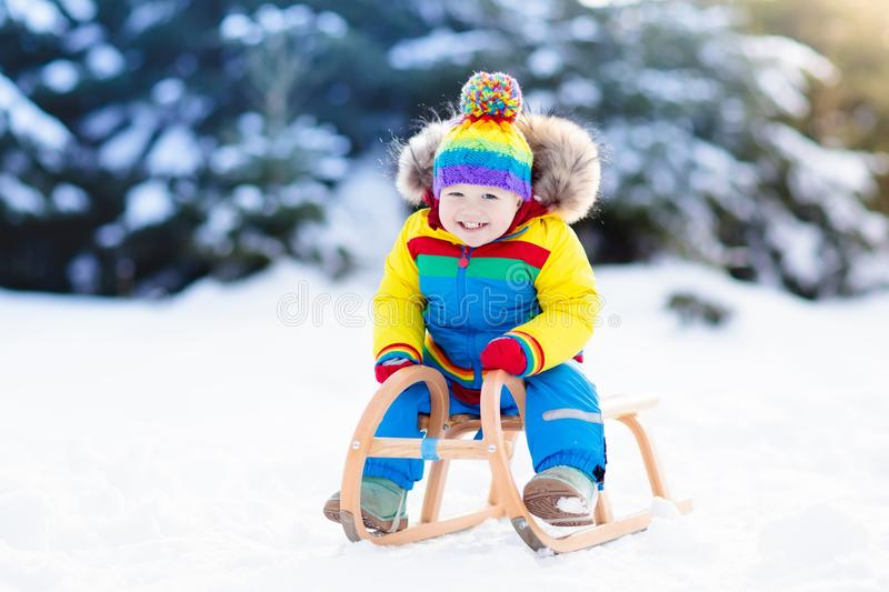 Boy on sleigh ride. Child sledding. Kid with sledge. Little boy enjoying a sleigh ride. Child sledding. Toddler kid riding a sledge. Children play outdoors in royalty free stock images